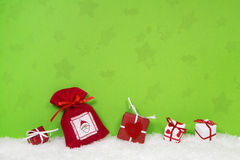Red and white christmas gifts on green background. Royalty Free Stock Image