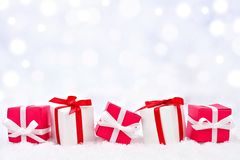 Red and white Christmas gifts in snow with twinkling background Royalty Free Stock Images