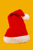 Red and white Christmas hat. On Yellow background Royalty Free Stock Image