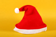 Red and white Christmas hat. On Yellow background Stock Photos