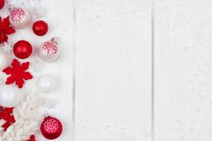 Red and white Christmas ornament side border over white wood Royalty Free Stock Photos