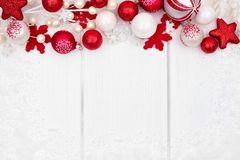 Red and white Christmas ornament top border over white wood Royalty Free Stock Images