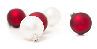 Red and White Christmas Ornaments on White. Three red and two white Christmas ornaments isolated on white background Stock Image