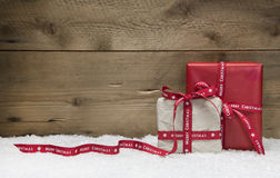 Red and white Christmas presents, with snow on wooden background Royalty Free Stock Photo