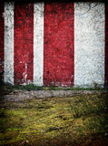 Red and White Circus Tent Background. Old grunge red and white stripes painted on a concrete wall of circus building, background Royalty Free Stock Image