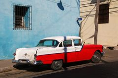 Red and white classic car in front of blue building Royalty Free Stock Photo