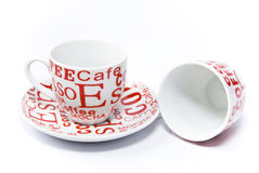 Red and white coffee cups. One of which is on the saucer, the other upside down, on a white background royalty free stock photo