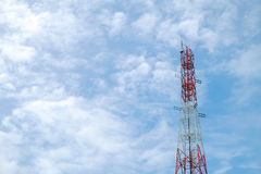 Red and white color antenna repeater tower on blue sky Royalty Free Stock Image