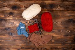 Red and white colored balls of thread, knitting needles and knitted socks on a wooden background stock images