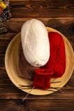 Red and white colored balls of thread and knitting needles with a knitting on a wooden background stock images