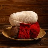 Red and white colored balls of thread and knitting needles with a knitting on a wooden background royalty free stock photos
