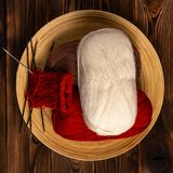 Red and white colored balls of thread and knitting needles with a knitting on a wooden background stock photos