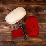 Red and white colored balls of thread and knitting needles with a knitting on a wooden background royalty free stock images