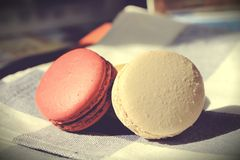Red and white colored macaroons on plate mat with vintage effected Stock Images