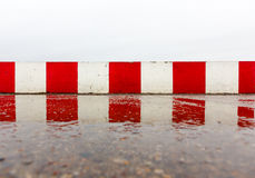 Red white concrete wall on the asphalt Stock Photos