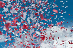 Red and White Confetti in the Air. Red and white strips of paper confetti fill the air with a blue sky and white clouds in the background Stock Photography
