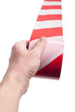 Red white cordon tape in hand Stock Photos