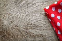 Red white cotton folded polka-dot tablecloth on wooden board cop. Y space Royalty Free Stock Photography