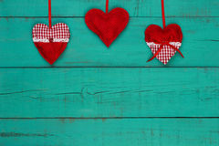 Red and white country hearts hanging by ribbon on antique teal blue sign Stock Photography
