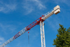 Red and White Crane on Blue Sky with Clouds. Detail of a red and white crane on blue sky with clouds and a green tree. Construction site Royalty Free Stock Photography