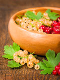 Red and white currant in wooden bowl Stock Photo