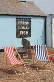 Red and white deckchairs sitting on shingle beach with a Fresh fish sign royalty free stock photos