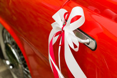 Red and white decorative wedding ribbons on a door handle of a red vintage car Royalty Free Stock Images