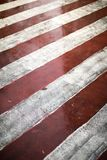 Red and white diagonal road markings for fire trucks. Rainy weather on a city street Royalty Free Stock Images