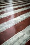 Red and white diagonal road markings for fire trucks. Rainy weather on a city street Stock Images