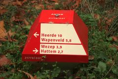 Red and white direction sign in the shape of the mushroom for cyclist at the Veluwe in the Netherlands. Red and white direction sign in the shape of the royalty free stock image