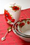 Red&white dishware. Dishware with red&white floral pattern of poppy on red linen Stock Photos