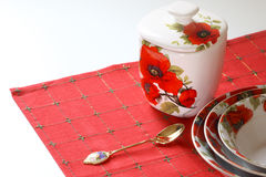 Red&white dishware. Dishware with red&white floral pattern of poppy on red linen Stock Images