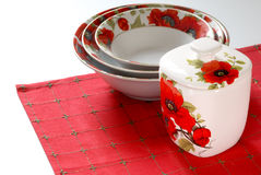 Red&white dishware. Dishware with red&white floral pattern of poppy on red linen Royalty Free Stock Photos