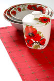 Red&white dishware. Dishware with red&white floral pattern of poppy on red linen Royalty Free Stock Image
