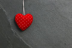 Red with White Dots Love Valentine's heart hanging on grey slate Stock Photo