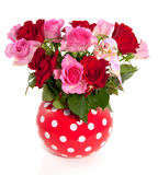A red white dotted vase with a bouquet of roses. A red white dotted vase with a bouquet of pink and red roses and a decoration bird Royalty Free Stock Image