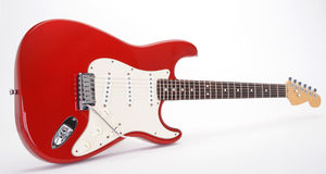 Red and white electric guitar. With studio background Royalty Free Stock Image