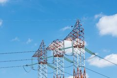 Red white electricity pylons, blue sky with white clouds stock images