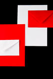 Red and white envelopes on black. With space for text Stock Image