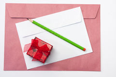 Red and white envelopes with a wooden pen and red gift box Stock Photography