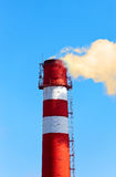 Red and white factory chimney with smoke against sky Royalty Free Stock Image