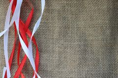 Red and white festive ribbons, threads against the texture of brown old linen cloth, linen natural material with a coarse perpendi. Cular interlacing of fabric Royalty Free Stock Image