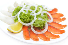 Red and white fish with greenery on plate Stock Photos