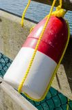 Red and White Fishing Buoy. Close up of a Colourful Fishing Buoy Hanging from the Fence of a Wooden Pier in Sooke Harbour, BC, Canada royalty free stock photo