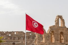 The red and white flag of Tunisia, on the background are ruins of the Roman Amphitheatre of El Jem, Tunisia, Africa royalty free stock photo