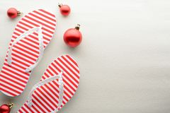 Red and white flip flops and Christmas ornaments. Red and white flip flops and Christmas y ornaments stock photography