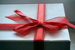 Red and white gift box with a ribbon on the top in a shape of great topknot Stock Photos