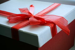 Red and white gift box with a ribbon on the top in a shape of great topknot Royalty Free Stock Photo