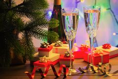 Red and white gift boxes under the Christmas tree. Champagne in two beautiful glasses. A nice gift for a holiday. royalty free stock photography