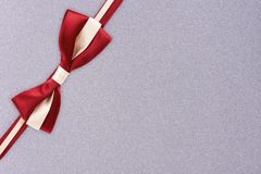 Red and white gift ribbon on a silver textured pattern background. stock photo